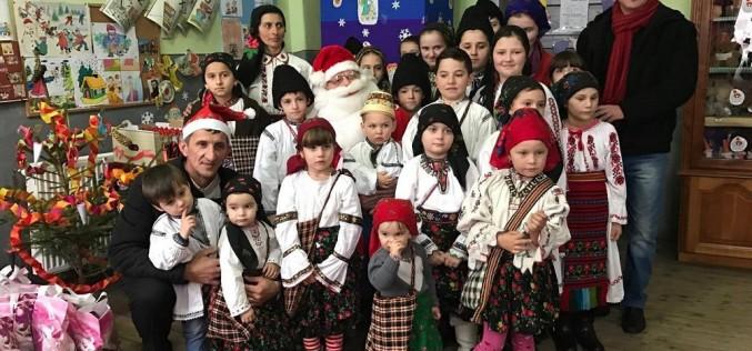 În straie populare, copiii din Strâmbu au primit cadouri de la Moș Crăciun – FOTO/VIDEO